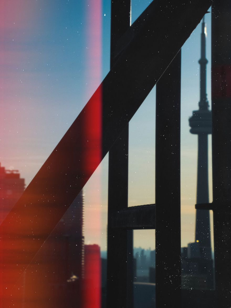 shot of CN Tower behind metal stairs on top of a tall crane
