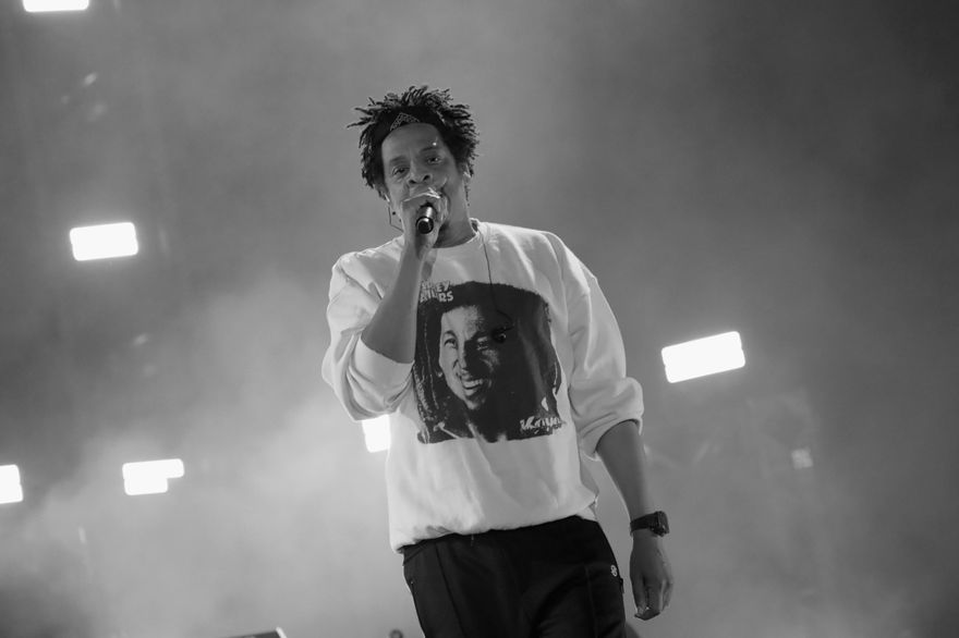 black and white image of Jay-Z performing live on stage while holding a mic and wearing a Bob Marley sweater