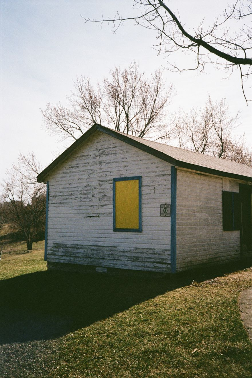 photo of old white shed with yellow wodden sealed window located on a park shot with film camera