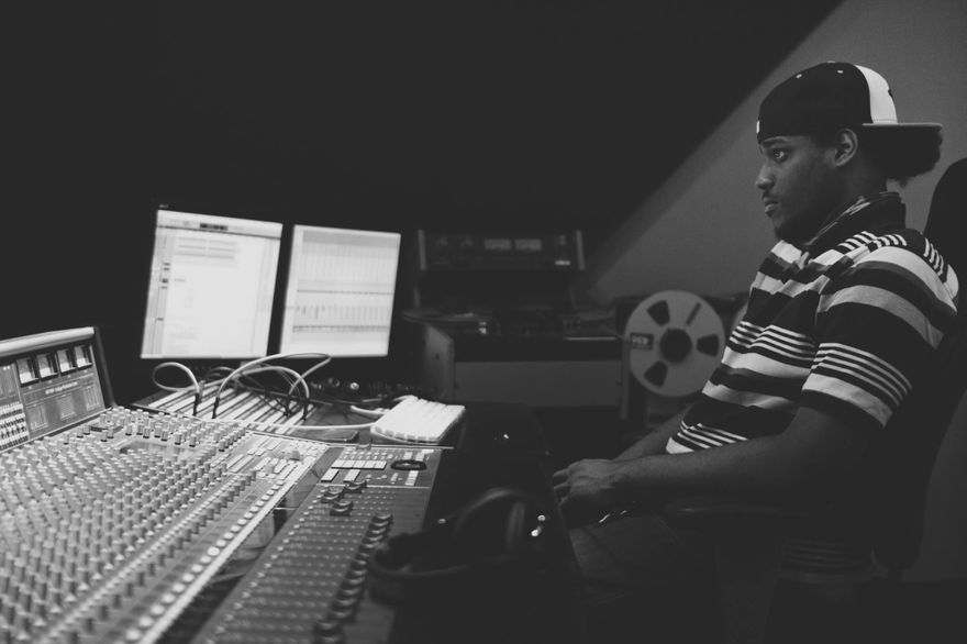 """Black and white photo of Franz """"GK"""" Liverpool sitting in a recording studio in front of a mixing board"""