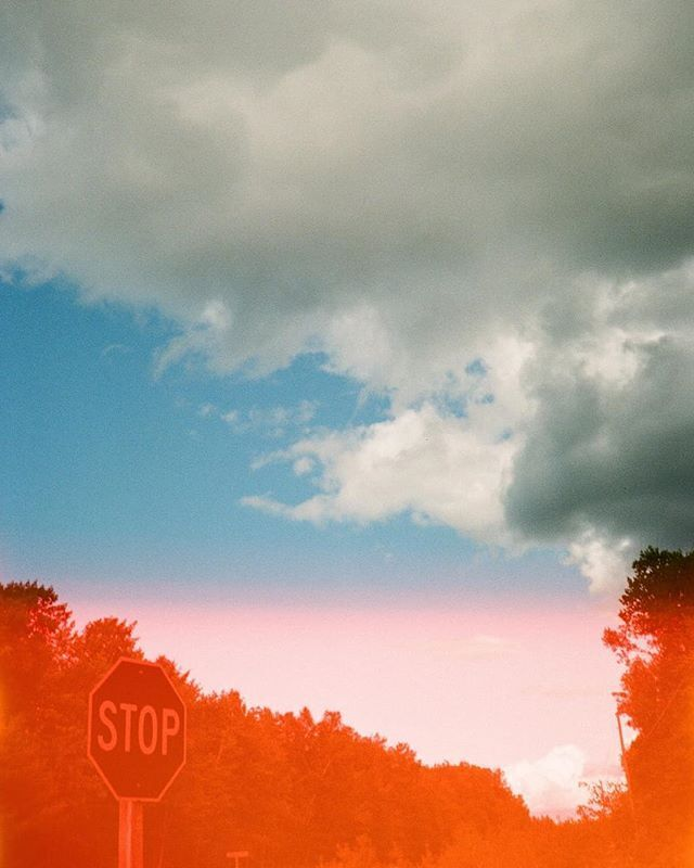 photo of blue cloudy sky with a road stop sign located bottom left of the photo. Photo was shot on film camera, with bottom part of photo containing red light leak