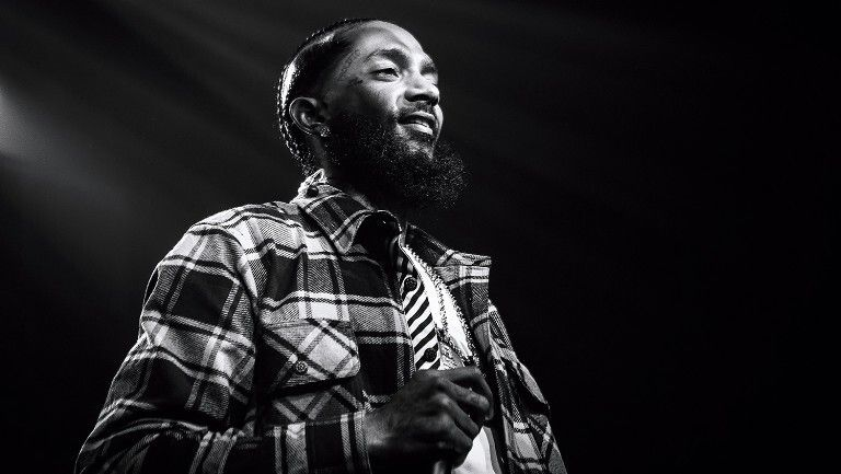 Black and white photo of Nipsey Hussle smiling on stage while holding microphone