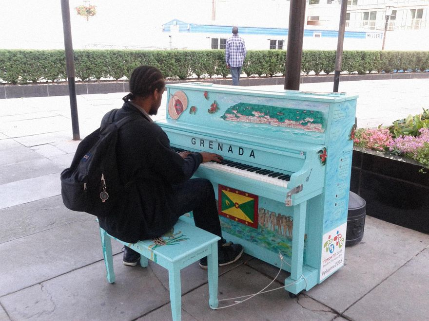 """Franz """"GK"""" Liverpool in Grenada, playing a music on a baby blue piano, outdoors. He is wearing a backpack."""