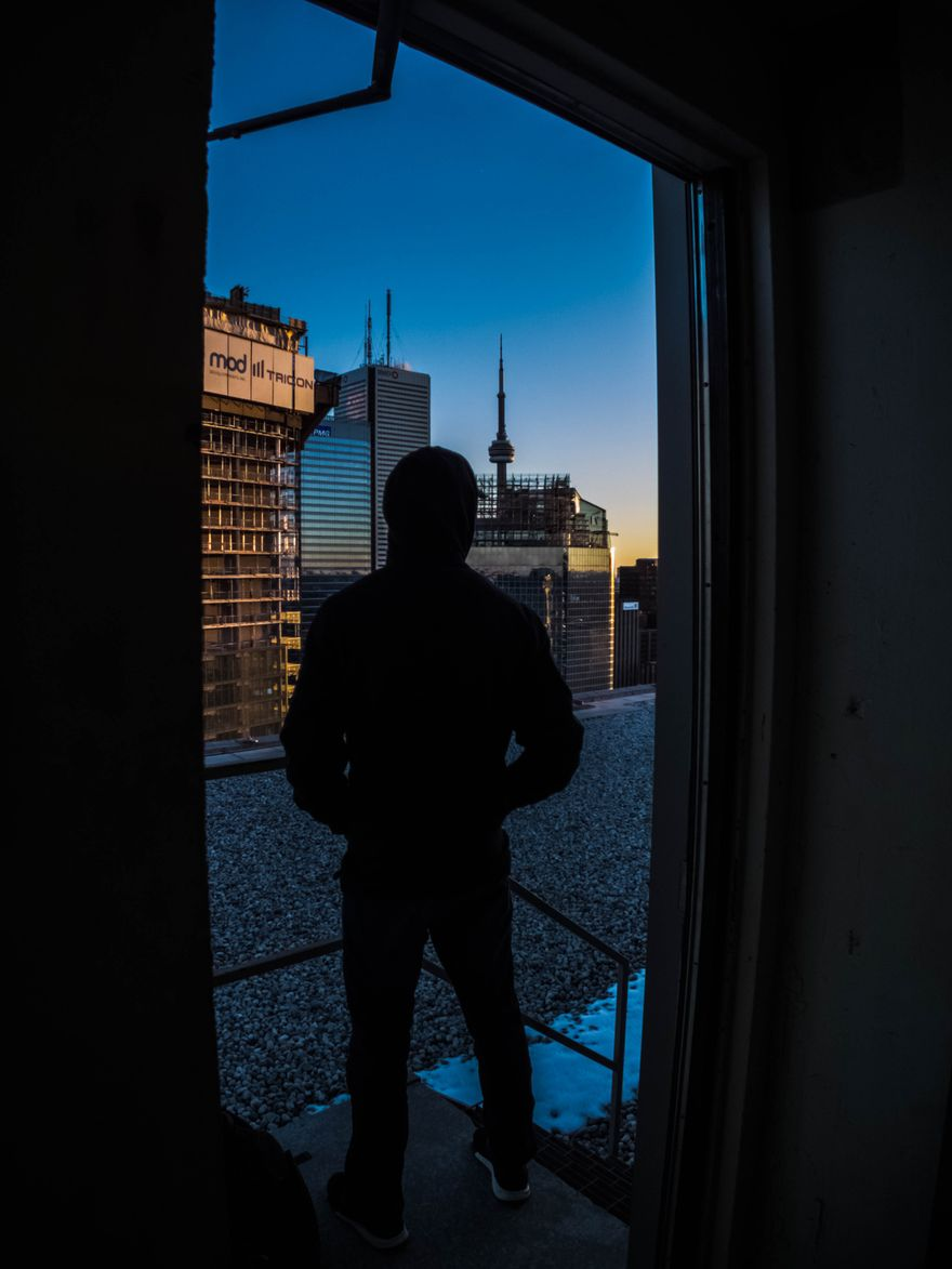 47mind's friend Ricky, standing on rooftop of Toronto skyscraper, in front of an open building door that leads outside to the rooftop